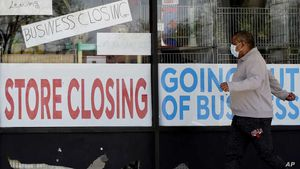 A man looks at signs of a closed store due to COVID-19 in Niles, Ill, May 21, 2020.   U.S. businesses shed 2.76 million jobs in May, as the economic damage from the historically unrivaled coronavirus outbreak stretched into a third month.
