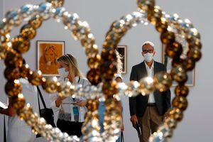 Visitors look at the sculpture 'Noeud Sauvage' by French artist Jean-Michel Othoniel during the preview of the 22nd edition of the Art Paris art fair at the Grand Palais in Paris, on September 9, 2020. Photo by THOMAS SAMSON/AFP via Getty Images.